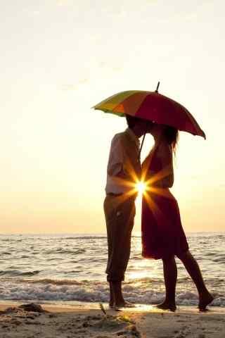 沙滩伞下亲吻的情侣
