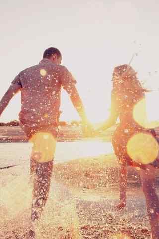 手牵手漫步在沙滩上的欧美情侣