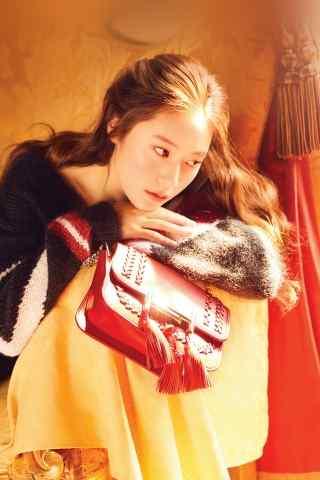 长发美女趴在沙发上暖色调手机壁纸